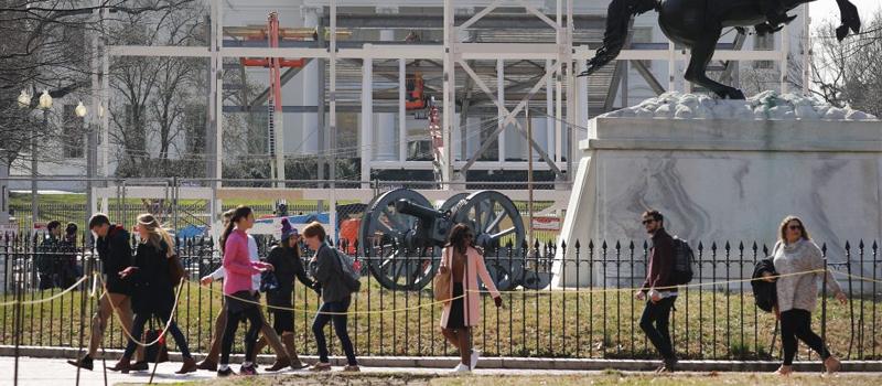 Unas personas pasan por Lafayette Park y al fondo se ven rejas y otros materiales de construcción frente a la Casa Blanca, mientras siguen los trabajos para desmantelar las gradas y el escenario montados para la toma de posesión del presidente Donald Trump