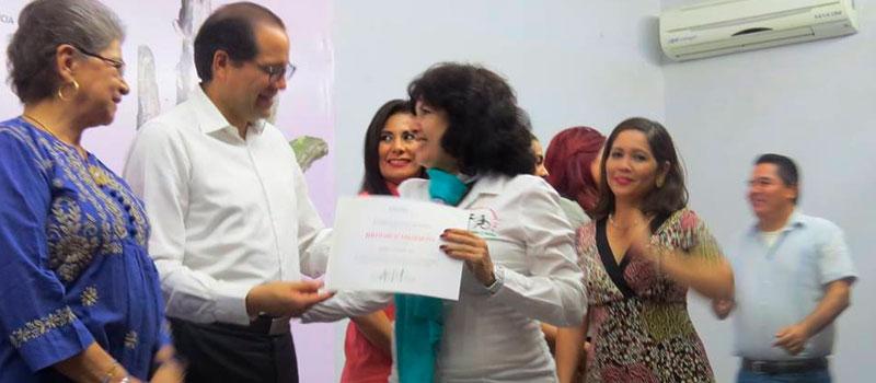 El gobernador José Ignacio Peralta Sánchez, entrega un reconocimiento por su labor a Adela Madrigal Trujillo, presidenta de Razón y Corazón IAP.